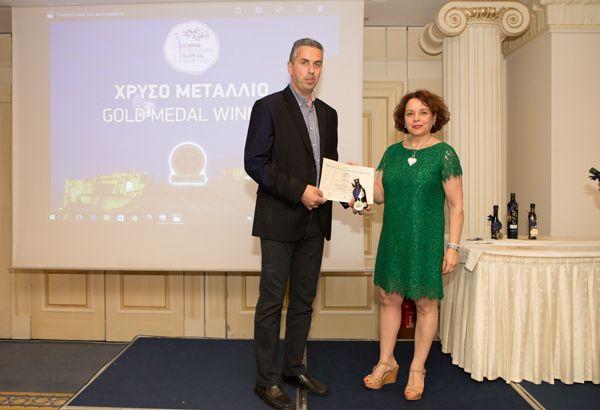 Η-διευθύντρια-του-ATHΙΟΟC-Μαρία-Κατσούλη-απονέμει-στον-Μιχαήλ-Τζωρτζή-το-χρυσό-μετάλλιο