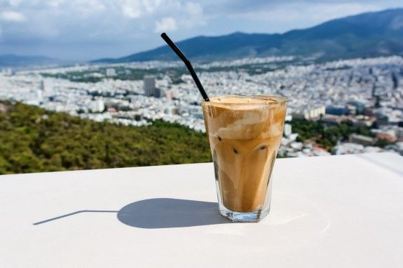 91187223 - ice frappe coffee and view of town of athens for background.
