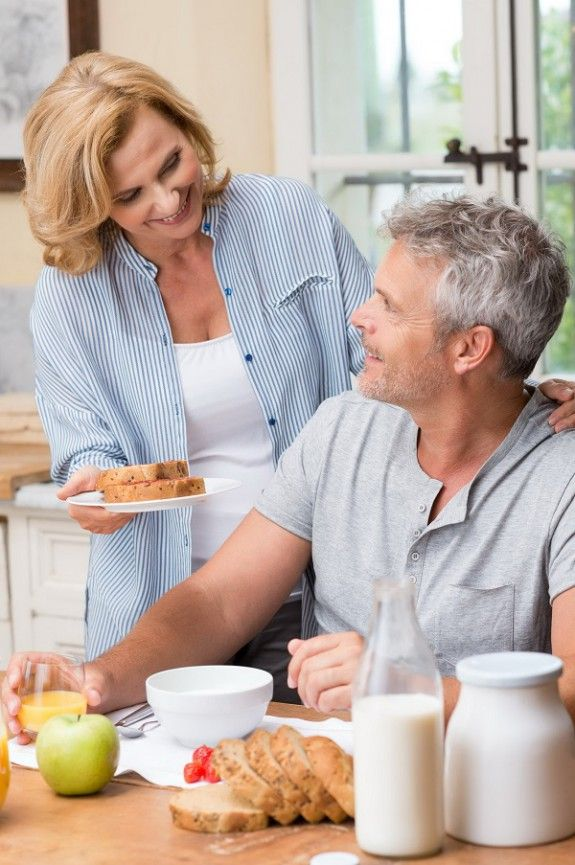 31178958 - smiling woman serves breakfast to her husband in morning