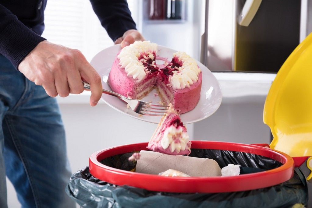 92388745 - close-up of a human hand throwing cake in trash bin