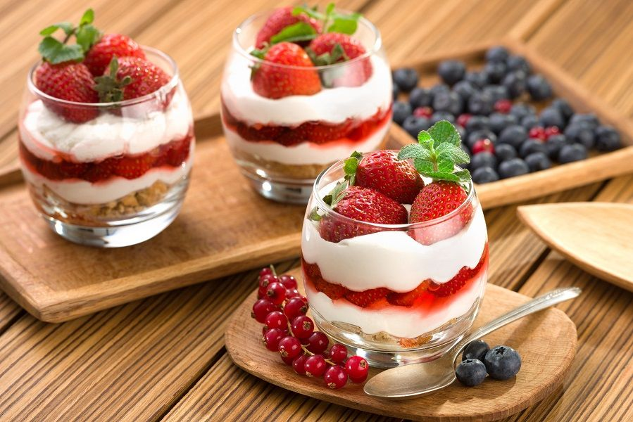90058848 - strawberrie dessert, cheesecake, trifle, parfaits on wooden background.