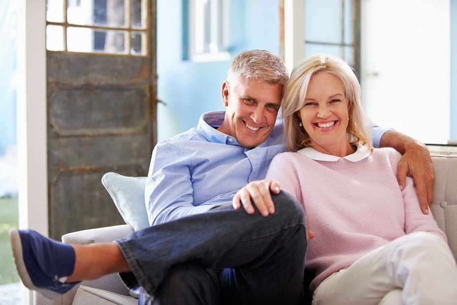 41402462 - portrait of smiling mature couple sitting on sofa at home