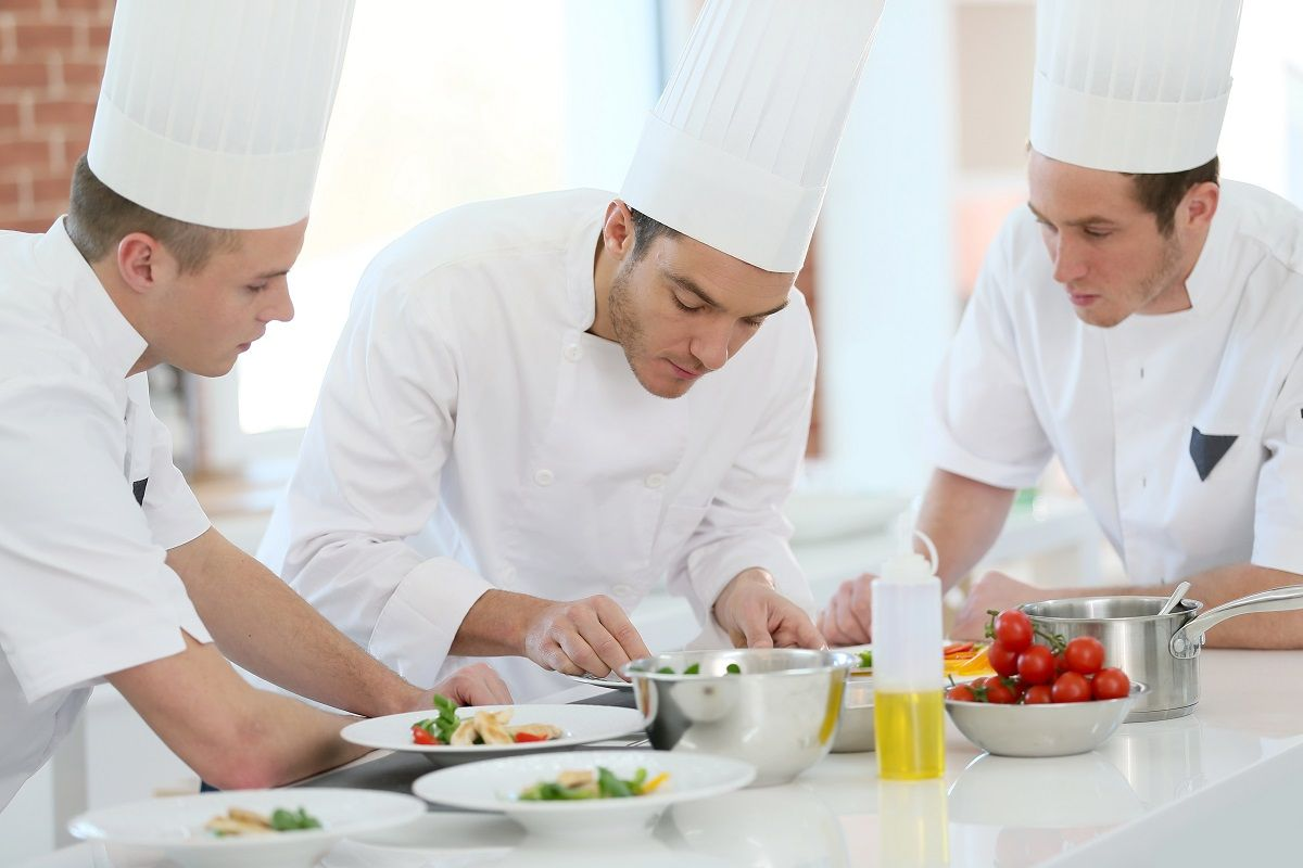 Chef training students in restaurant kitchen