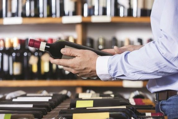 62419944 - midsection of male customer holding wine bottle in shop