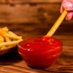 Hand with fresh french fry dipped into the tomato sauce