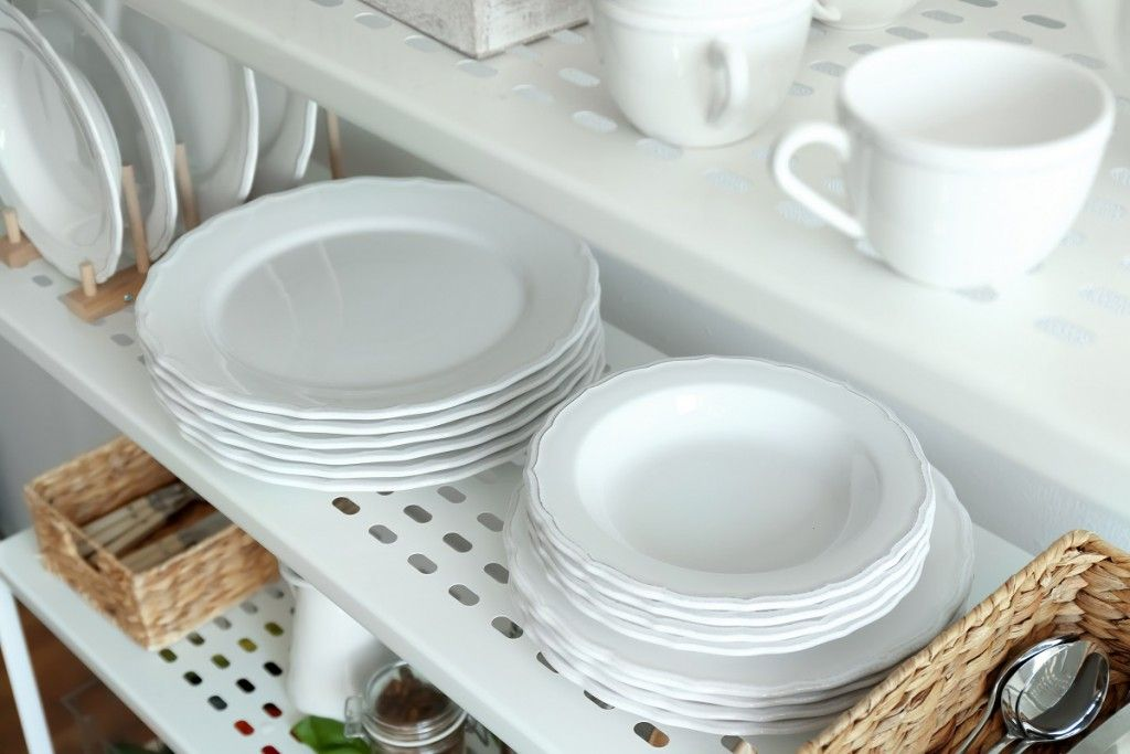Different plates on shelf of storage stand