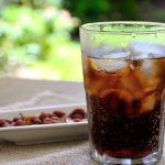 65988925 – fresh cola in a glass with a snak of peanuts on a wood table